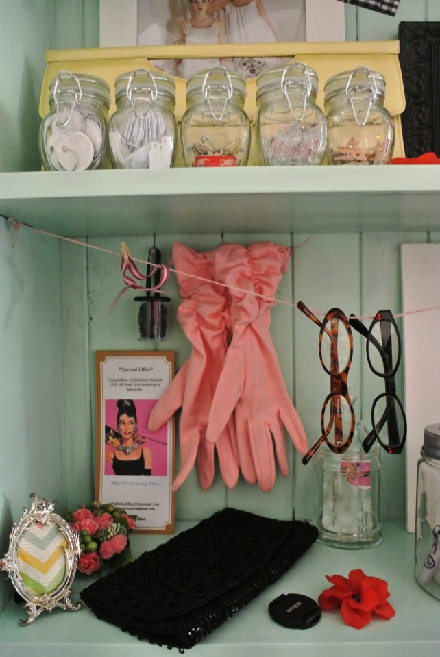 "I love these pink vintage gloves, and they're perfect on display.  The ""clothesline"" is made from pink string and tacks, and I've hung some glasses for sale on them.  In the background are my brochures and cards."