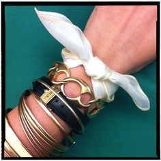 Small handkerchief tied at the end of your arm party.  Need: multiple cool bracelets, small square hanky or scarf.